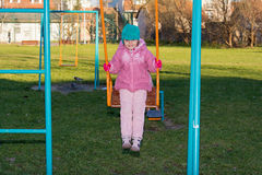 Petite fille sur l'oscillation au terrain de jeu Photographie stock