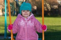 Petite fille sur l'oscillation au terrain de jeu Photos libres de droits