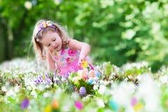 Petite fille sur la chasse à oeuf de pâques Image stock