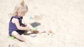 Petite fille sur la plage jouant dans des jouets pour le sable banque de vidéos