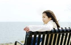 Petite fille sur le banc par le rivage de lac Photographie stock