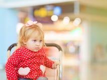Petite fille sur le chariot de bagage dans l'aéroport Image stock
