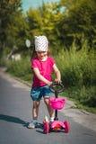 Petite fille sur le scooter Photographie stock libre de droits