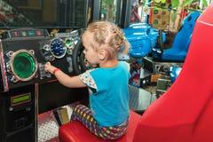 Petite fille sur le simulateur de jeu Images stock