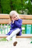 Petite fille sur un banc Photographie stock