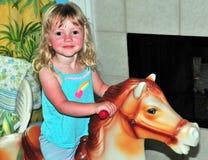 Petite fille sur un cheval d'oscillation photo libre de droits