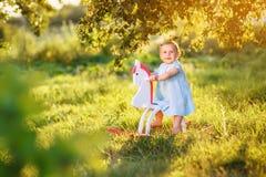 Petite fille sur un cheval de jouet Images stock