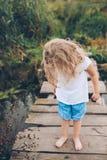 Petite fille sur un pilier en bois Photos stock