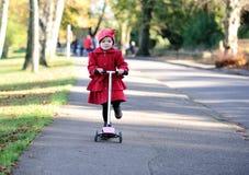 Petite fille sur un scooter Photographie stock libre de droits