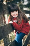 Petite fille sur une barrière Photo stock