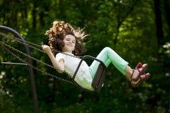 Petite fille sur une oscillation en parc d'été Images libres de droits