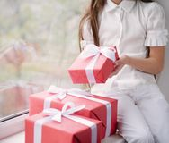 Petite fille tenant dans des mains une boîte avec des cadeaux de Noël Images libres de droits