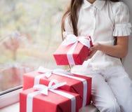Petite fille tenant dans des mains une boîte avec des cadeaux de Noël Photographie stock