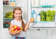 Petite fille tenant des pommes de réfrigérateur image stock
