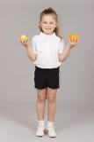 Petite fille tenant deux pommes Image libre de droits