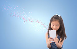 Petite fille tenant et regardant le téléphone intelligent avec l'écoulement graphique de flocon de neige d'effet du téléphone int Photos stock