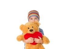 Petite fille tenant l'ours et le coeur de nounours Images stock