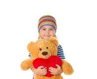 Petite fille tenant l'ours et le coeur de nounours Photos stock