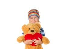 Petite fille tenant l'ours et le coeur de nounours Photographie stock libre de droits