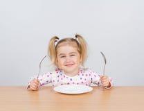Petite fille tenant la fourchette et la cuillère avec photos stock