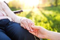 Petite-fille tenant la main de la grand-mère en nature de fauteuil roulant au printemps Images libres de droits