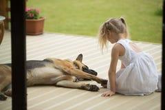 Petite fille tenant la patte de chiens se reposant près de l'animal familier sur le porche Photographie stock