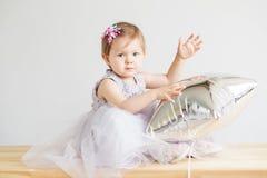petite fille tenant le ballon en forme d'étoile argenté Image libre de droits