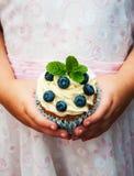 Petite fille tenant le petit gâteau Photographie stock libre de droits