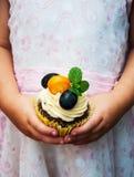 Petite fille tenant le petit gâteau Photos stock
