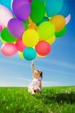 Petite fille tenant les ballons colorés. Enfant jouant sur un vert photos stock