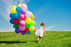 Petite fille tenant les ballons colorés. Enfant jouant sur un vert Images stock