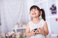Petite fille tenant un vieil appareil-photo Photos libres de droits