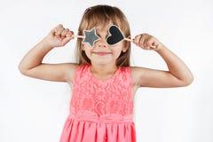 Petite fille tenant une étoile et un coeur Photos stock