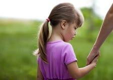 Petite fille tenant une main de sa mère Conce de relations de famille Photo stock