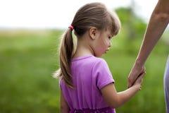 Petite fille tenant une main de sa mère Conce de relations de famille Photographie stock