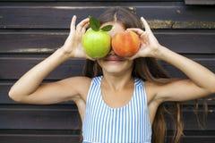 Petite fille tenant une pomme verte et une pêche Photo stock