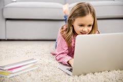 Petite fille travaillant avec un ordinateur portatif Image libre de droits