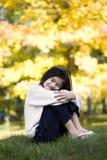 Petite fille étreignant des genoux sur la pelouse Images libres de droits