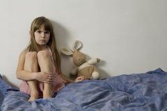 Petite fille triste avec des lièvres photo libre de droits