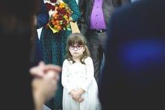 Petite fille triste dans la robe blanche dans la foule au mariage photos libres de droits
