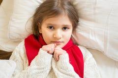Petite fille triste dans le chandail blanc se trouvant sous la couverture au lit Image stock