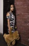 Petite fille triste embrassant son ours de nounours fille punie tenant le mur de briques proche Photographie stock libre de droits