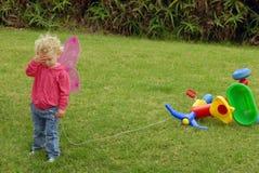 Petite fille triste jouant avec le tricycle coloré photographie stock libre de droits