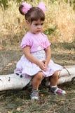 Petite fille triste s'asseyant sur le logarithme naturel Image libre de droits