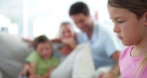 Petite fille triste se sentant à gauche hors de sa famille banque de vidéos