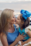 Petite fille trois ans se reposant sur le recouvrement de la mère avec de longs cheveux blonds Photo stock
