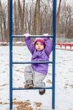 Petite fille un an montant l'échelle dehors dans le terrain de jeu de parc d'hiver Image libre de droits