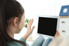 Petite fille utilisant la causerie visuelle sur le comprimé à la maison photo libre de droits