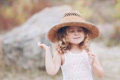 Petite fille utilisant un chapeau à l'extérieur Images stock