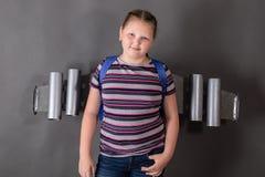 Petite fille vaillante forte avec un jetpack sur le sien de retour sur le fond gris images stock